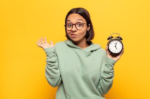 의아해하고 혼란스러워하는 젊은 라틴 여자, 의심, 가중치 또는 재미있는 표현으로 다른 옵션 선택