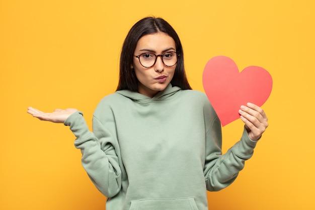 困惑して混乱していると感じている若いラテン女性、疑わしい、重みを付けたり、面白い表現でさまざまなオプションを選択したりする