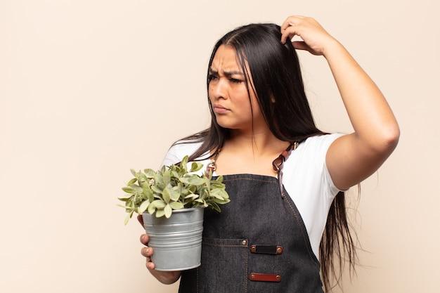 Молодая латинская женщина чувствует себя озадаченной и сбитой с толку, почесывает голову и смотрит в сторону