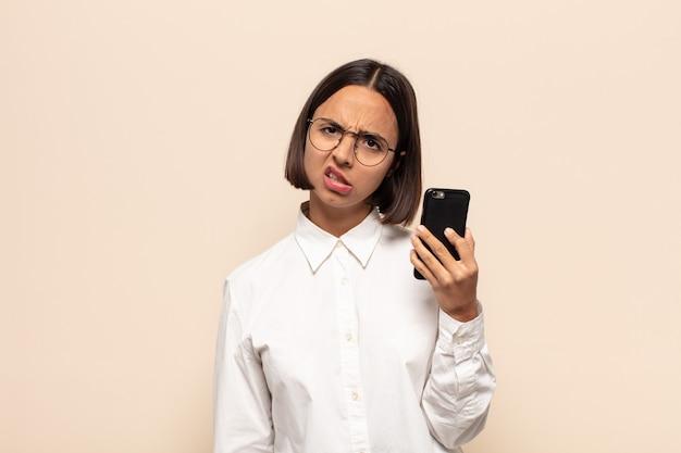 Молодая латинская женщина недоумевает и смущена, с немым ошеломленным выражением лица смотрит на что-то неожиданное