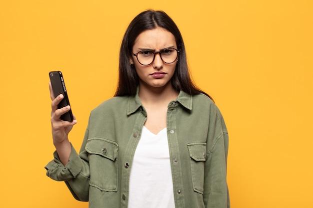 Молодая латинская женщина с недоумением и недоумением смотрит на что-то неожиданное с тупым ошеломленным выражением лица.