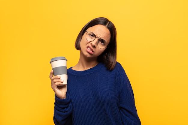 困惑して混乱している若いラテン女性は、予想外の何かを見ている愚かな、唖然とした表情で