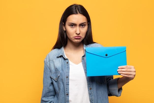 不幸な表情で悲しみと泣き言を感じ、否定的で欲求不満の態度で泣いている若いラテン女性