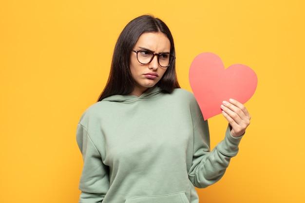 若いラテン女性は、悲しみ、動揺、または怒りを感じ、否定的な態度で横を向いて、意見の相違に眉をひそめています