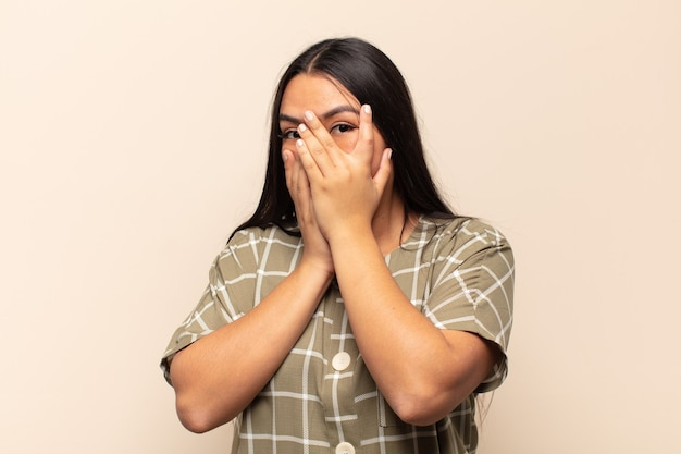 Молодая латинская женщина чувствует себя испуганной или смущенной, подглядывает или шпионит с полузакрытыми руками глазами