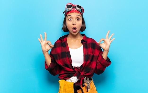 Молодая латинская женщина чувствует себя потрясенной, пораженной и удивленной, показывая одобрение, делая знак