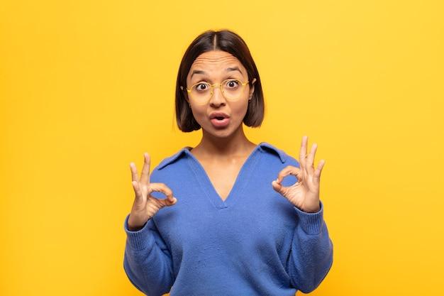 若いラテン女性はショックを受け、驚き、驚きを感じ、両手で大丈夫なサインをする承認を示しています