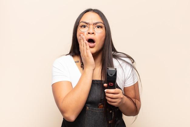 Молодая латинская женщина чувствует себя потрясенной и напуганной, выглядит испуганной с открытым ртом и руками по щекам
