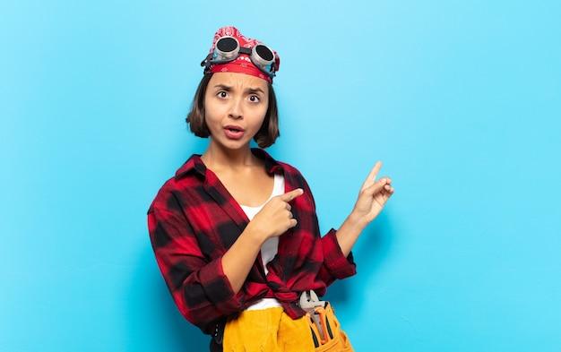 Молодая латинская женщина чувствует себя потрясенной и удивленной, указывая на место для копирования сбоку с изумленным взглядом с открытым ртом