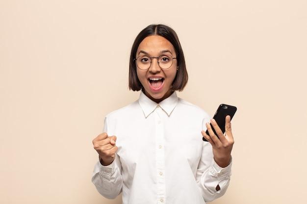 Молодая латинская женщина чувствует себя потрясенной, взволнованной и счастливой, смеется и празднует успех, говоря