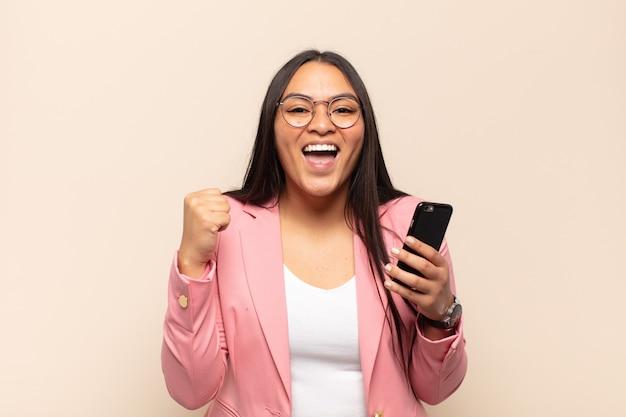 Молодая латинская женщина чувствует себя потрясенной, взволнованной и счастливой, смеется и празднует успех, говоря: