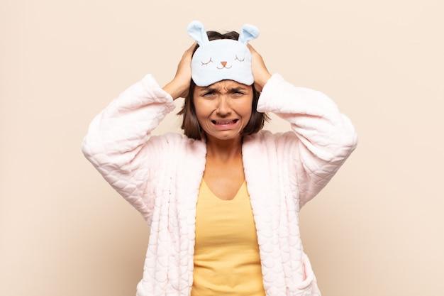 ストレスと欲求不満を感じ、手を頭に上げ、倦怠感、不幸、片頭痛を感じる若いラテン女性