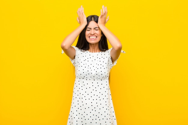 Young latin woman feeling stressed and anxious, depressed and frustrated with a headache, raising both hands to head on flat wall