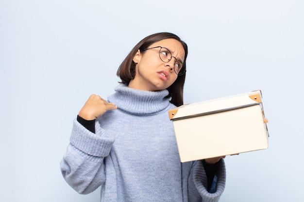 Молодая латинская женщина чувствует стресс, тревогу, усталость и разочарование, тянет за шею рубашки, выглядит разочарованной проблемой