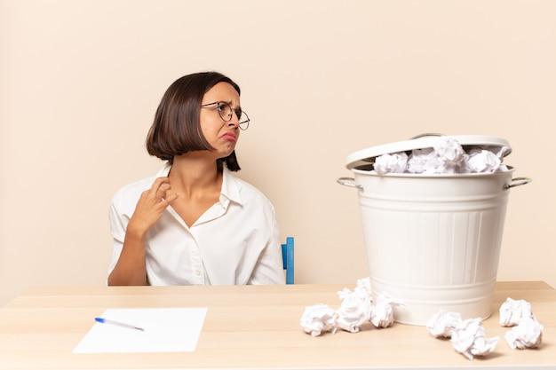 Молодая латинская женщина чувствует стресс, тревогу, усталость и разочарование, дергает за шею рубашки, выглядит разочарованной проблемой