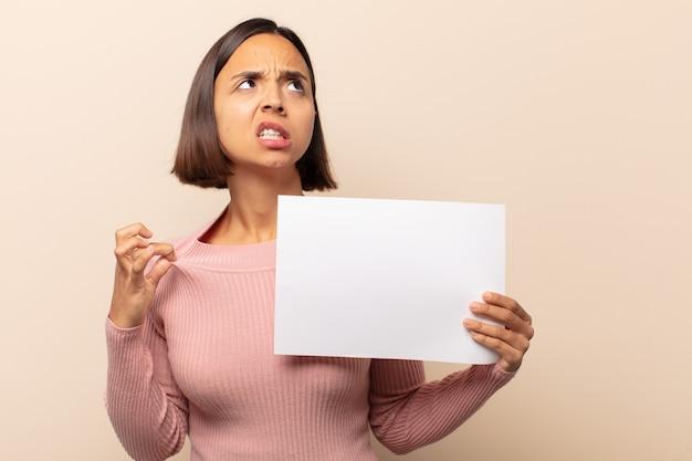 Молодая латинская женщина чувствует стресс, тревогу, усталость и разочарование, тянет рубашку за шею, выглядит разочарованной проблемой