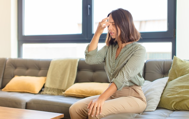 ストレス、不幸、欲求不満を感じ、額に触れ、激しい頭痛の片頭痛に苦しんでいる若いラテン女性