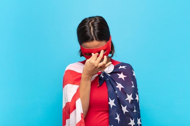 Молодая латинская женщина чувствует стресс, несчастье и разочарование, трогает лоб и страдает от сильной мигрени