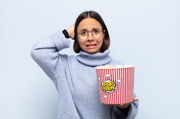 Молодая латинская женщина чувствует стресс, беспокойство, беспокойство или страх, с руками за голову, паникует из-за ошибки