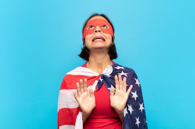 ラテン系の若い女性は、何か恐ろしいことを恐れて、愚かで怖がっていて、手を前に開いて「離れて」と言っています。