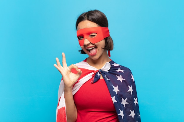 Молодая латинская женщина чувствует себя успешной и довольной костюмом американского супергероя
