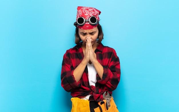 Молодая латинская женщина чувствует беспокойство, надежду и религиозность, верно молится, прижав ладони, умоляя о прощении