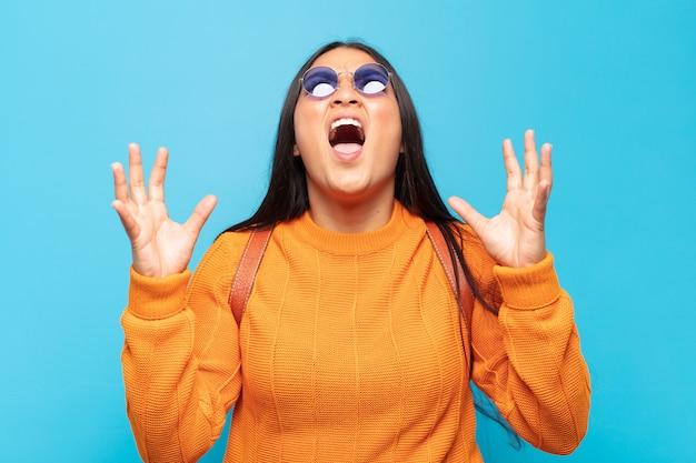 ラテン系の若い女性が猛烈に叫び、ストレスを感じ、空中に手を上げてイライラし、なぜ私が
