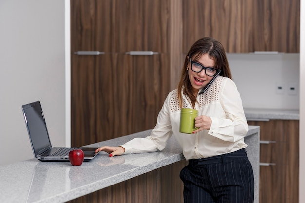 부엌에서 노트북으로 메일을 확인하면서 커피 한 잔을 마시는 젊은 라틴 여성