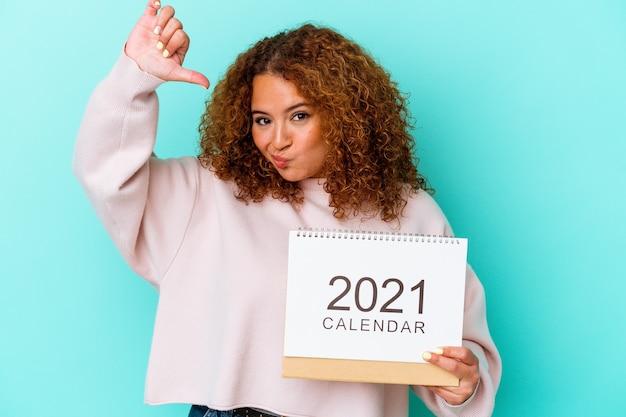 青い背景にカレンダーを持った若いラテン女性は、誇りと自信を感じ、模範に従う.