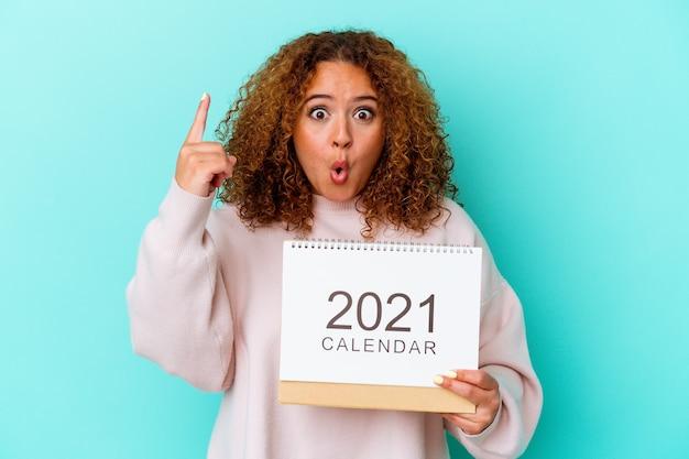 青の背景にカレンダーを持つ若いラテン女性が、創造性のコンセプト、素晴らしいアイデアを持っている。