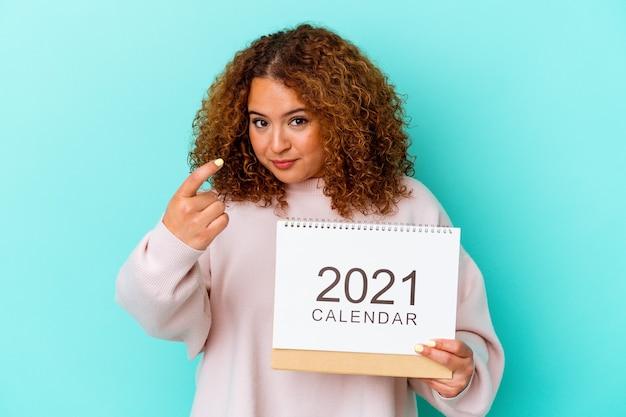 青い背景に分離されたカレンダーを持つ若いラテン女性が、近づいてくるようにあなたを指で指しています。