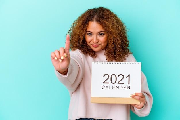指で番号 1 を示す青い背景に分離されたカレンダーを保持している若いラテン女性。