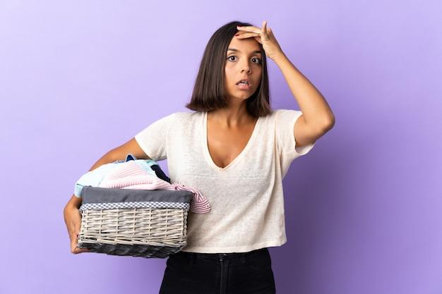 横を見ながら驚きのジェスチャーをしている紫で隔離の服のバスケットを保持している若いラテン女性
