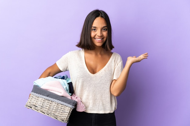広告を挿入するために手のひらに紫のcopyspace想像を保持に分離された服のバスケットを保持している若いラテン女性
