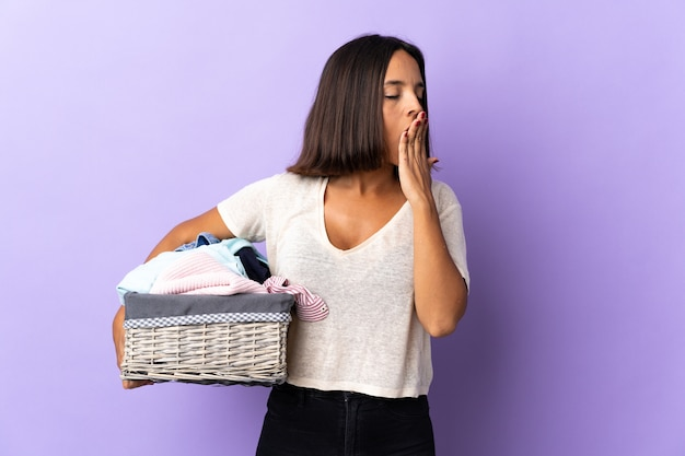 Молодая латинская женщина держит корзину с одеждой