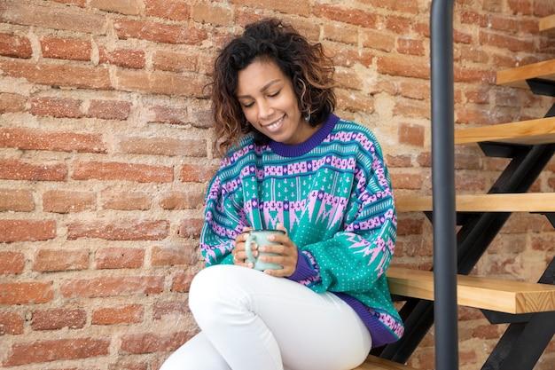 彼女の手でコーヒーカップを保持している若いラテン女性。彼女は家の階段に座っています。テキスト用のスペース。