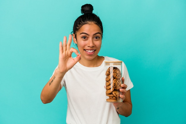 Молодая латинская женщина держит банку печенья, изолированную на синем фоне, веселый и уверенный, показывая одобренный жест.