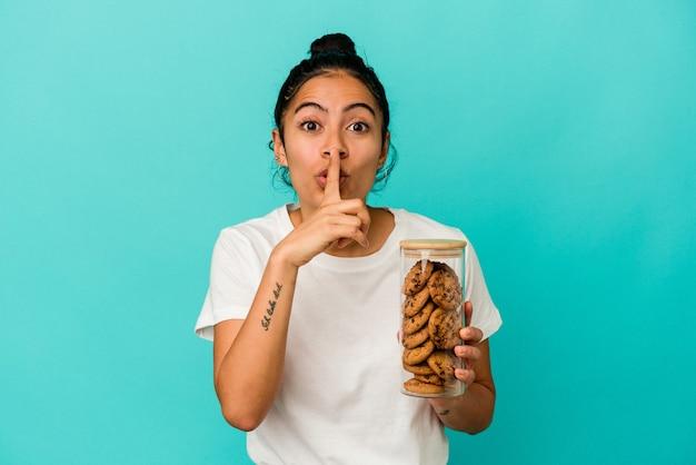 비밀을 유지하거나 침묵을 요구하는 파란색 배경에 고립 된 쿠키 항아리를 들고 젊은 라틴 여자.