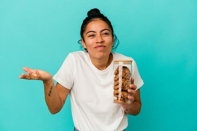 青い背景で隔離のクッキーの瓶を保持している若いラテン女性は肩をすくめると混乱した目を開いています。
