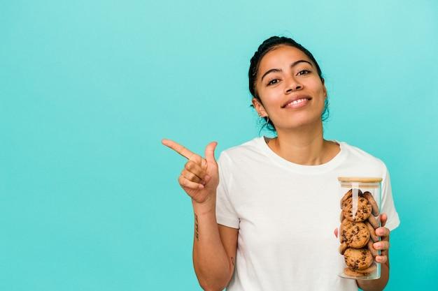 空白のスペースで何かを見せて、笑顔で脇を指して、青い背景で隔離のクッキーの瓶を保持している若いラテン女性。