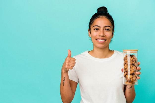 笑顔と親指を上げて青い背景で隔離のクッキーの瓶を保持している若いラテン女性 Premium写真
