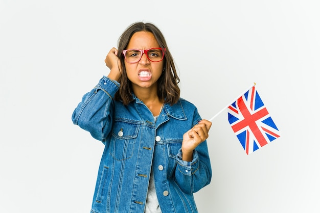 너무 큰 소리를 듣지 않으려 고 손으로 귀를 덮고 영어 깃발을 들고 젊은 라틴 여자.