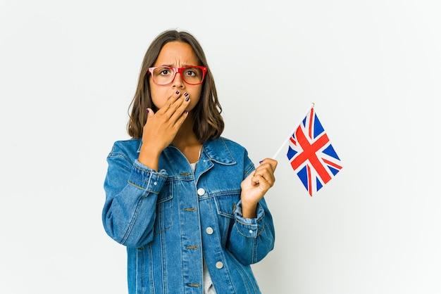 Молодая латинская женщина, держащая английский флаг, изолирована на белом прикрытии рта руками, выглядящими обеспокоенными.