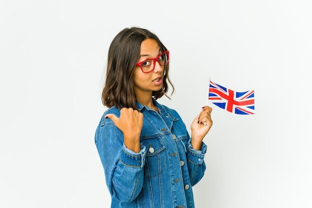 엄지 손가락으로 멀리, 웃음과 평온한 흰색 점에 고립 된 영어 깃발을 들고 젊은 라틴 여자.