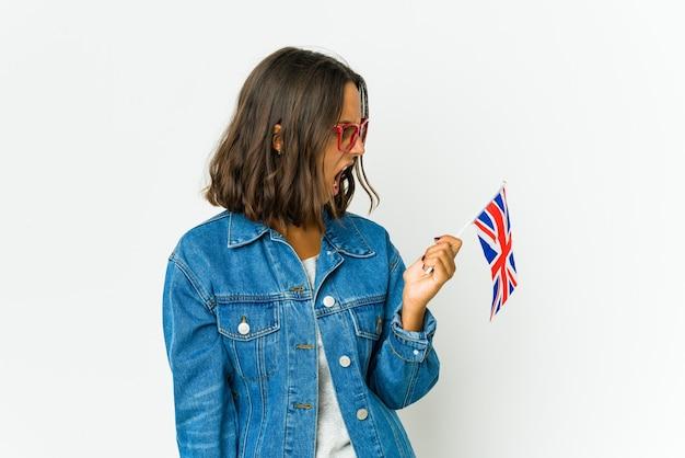 매우 화가, 분노 개념, 좌절 흰색 소리에 고립 된 영어 깃발을 들고 젊은 라틴 여자.
