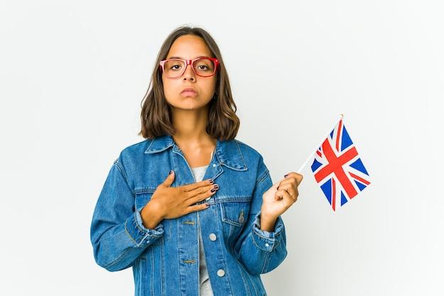 誓いを立て、胸に手を置いて、白で隔離の英語の旗を保持している若いラテン女性。