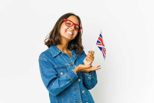 손바닥에 복사 공간을 잡고 흰 벽에 고립 된 영어 깃발을 들고 젊은 라틴 여자.
