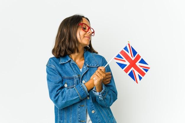 白い壁に隔離された英語の旗を保持している若いラテン女性は、のんびりと幸せに笑って抱擁します。
