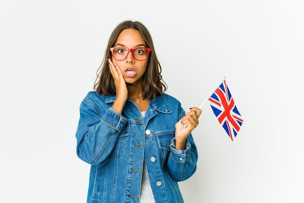 白い壁に分離された英語の旗を保持している若いラテン女性は、手のひらにコピースペースを保持していることに感銘を受けました。