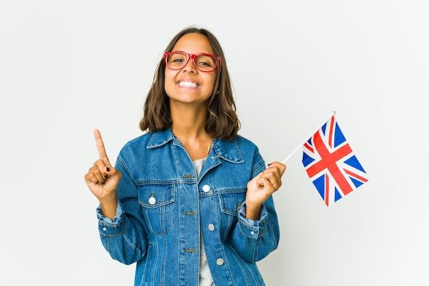 흰 벽에 고립 된 영어 깃발을 들고 젊은 라틴 여자는 빈 공간을 보여주는 두 앞 손가락으로 나타냅니다.